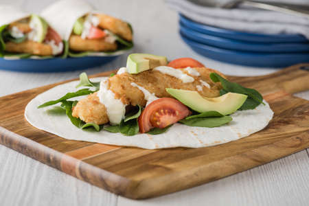 Fish finger wraps with avocado and tomato serves on wooden cheese platter