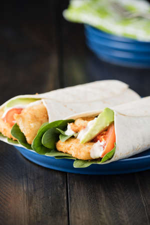 fishfinger: Crumbed fish fillet burrito with avocado and tomato on rustic background Stock Photo