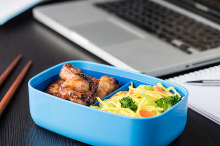 box: Chicken wings and noodles in bento box at office lunch