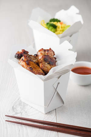 chinese drum: Asian chicken wings and noodles in take-out box with dipping sauce Stock Photo