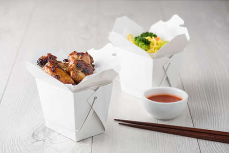 takeout: Asian chicken wings and noodles in take-out box with dipping sauce Stock Photo