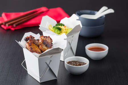 take away: Asian chicken wings and noodles in take-out box