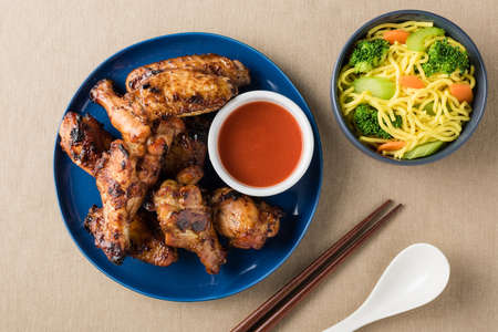 serves: Barbecue chicken wings serves noodles with hot dipping sauce