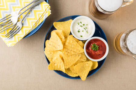 corn chip: Nachos with salsa and sour cream dips at beer pub garden