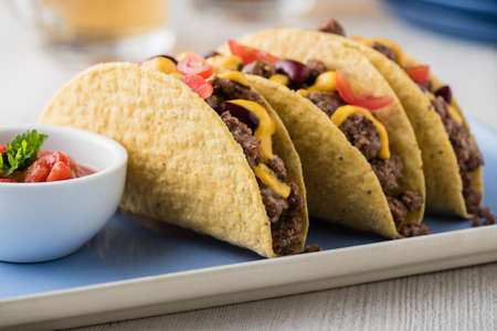 cheddar cheese: Beef tacos with salsa,cheddar cheese, tomato, beans and beer