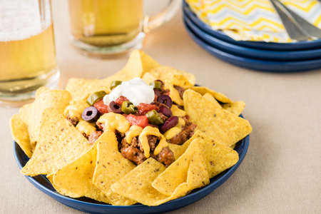 cheddar cheese: Nachos with beef, jalapeno. beans cheddar cheese and sour cream at beer pub garden