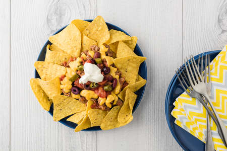 cheddar cheese: Beef nachos with  jalapeno, olives, tomato, beans cheddar cheese and sour cream Stock Photo