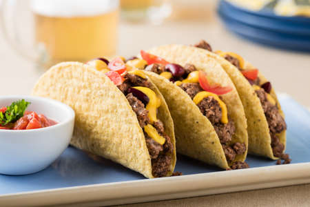 cheddar cheese: Mexican tacos with beef, cheddar cheese, tomato, beans and salsa dips at beer garden
