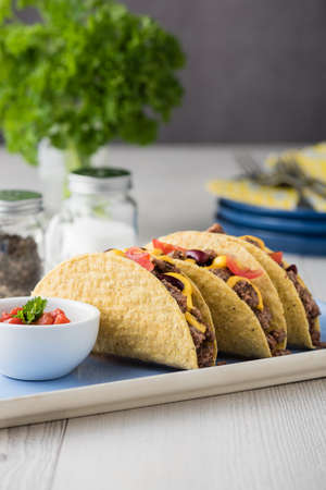 cheddar cheese: Beef tacos with salsa,cheddar cheese, tomato and beans