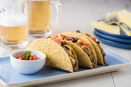 fingerfood: Beef tacos with salsa,cheddar cheese, tomato, beans and beer