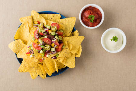 corn chip: Vegetarian nachos tomato, beans, capsicum, avocado, olive, jalapeno and dipping sauces Stock Photo