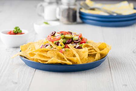 sauces: Vegetarian nachos tomato, beans, capsicum, avocado, olive, jalapeno and dipping sauces Stock Photo