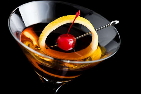 manhattan cocktail con limón y cereza marrasquino sobre fondo negro