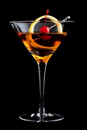 Manhattan cocktail with lemon and maraschino cherry on black background