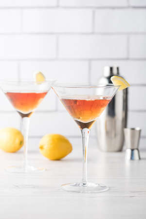 Fresh home made Manhattan cocktails with lemon and maraschino cherry