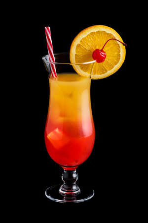 Tequila sunrise cocktail with garnish on black background Stock Photo