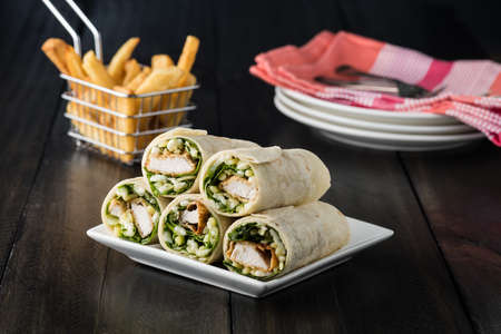 baby spinach: Breaded Chicken burrito Wrap With Fresh Lettuce Cheese on rustic background Stock Photo