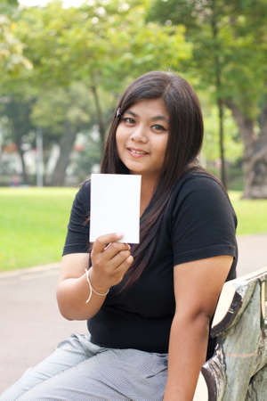 Women sitting in the park and hold a white card. Stock Photo - 8893769