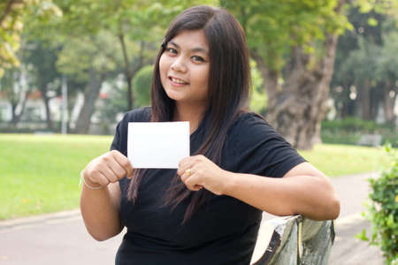 Women sitting in the park and hold a white card. Stock Photo - 8893739