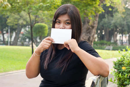 Women sitting in the park and hold a white card.  Stock Photo - 8893781