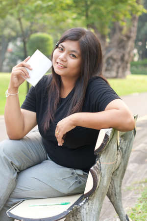 Women sitting in the park and hold a white card.  Stock Photo - 8893797