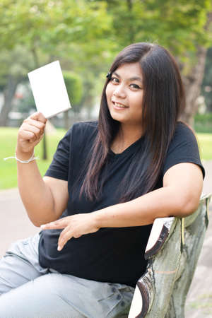 Women sitting in the park and hold a white card.  Stock Photo - 8893766