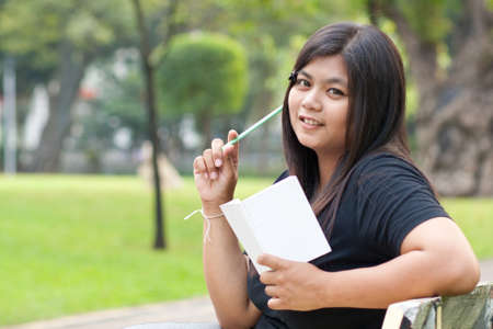 Women sitting in the park and hold a white card. Stock Photo - 8893770