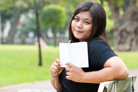 Women sitting in the park and hold a white card.  Stock Photo - 8893768