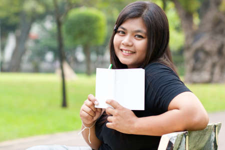 Women sitting in the park and hold a white card. Stock Photo - 8893743