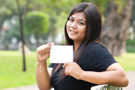 Women sitting in the park and hold a white card.  Stock Photo - 8893729