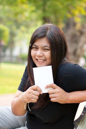 Women sitting in the park and hold a white card. Stock Photo - 8893742