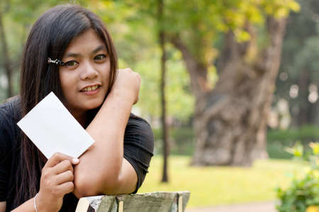 Women sitting in the park and hold a white card.  Stock Photo - 8893787