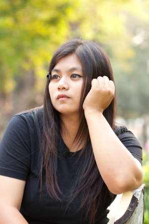 vago: Woman sitting in a park looking vacant