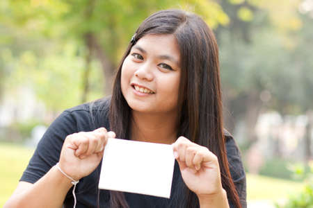 Women sitting in the park and hold a white card. Stock Photo - 8893734