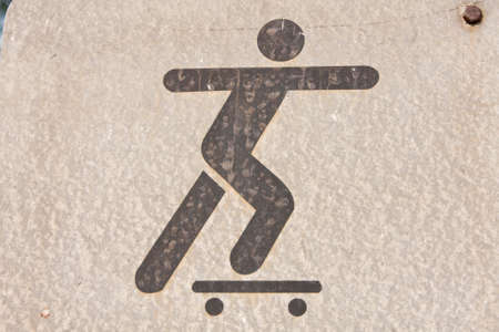 A symbol, people are playing skateboarding. On background