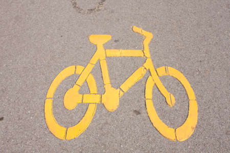 Yellow bike symbol. On the background in the park.  photo