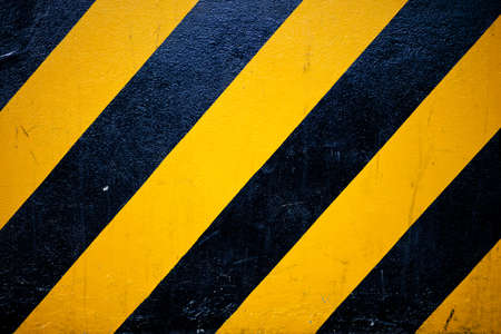 Black and yellow diagonally pattern which symbolizes a warning sign on a road. photo