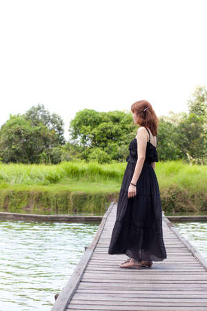 Woman standing in the middle of the bridge the pond in the park. Stock Photo - 10907346