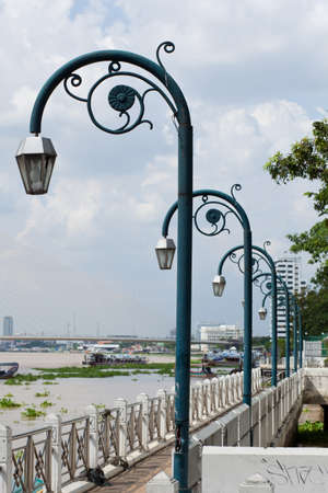 Lamps arranged in a row. Behind a bridge crossing the river. photo