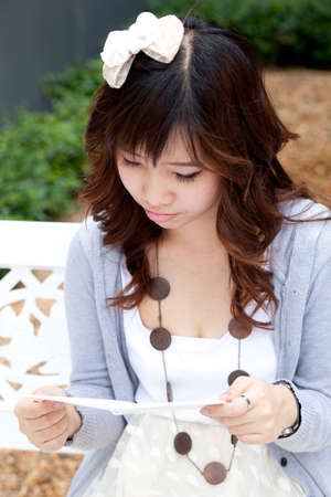 thai woman carry note paper and read note paper in garden.  photo