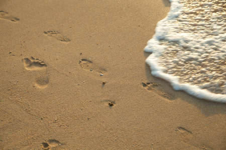 Footprints on the sand. The waves hitting the shore. Media and holidays. photo