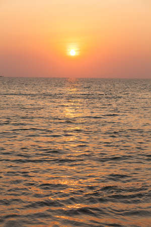 The sun goes down at sea, the sky is orange When the sun sets below  photo