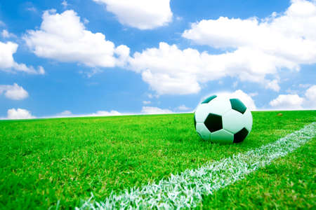 Soccer ball in grass. Behind the sky bright.