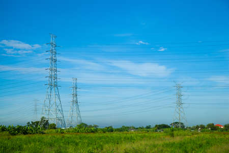 High voltage towers. The meadow below. Industry and nature coexist in appropriate Slightly cloudy sky. photo