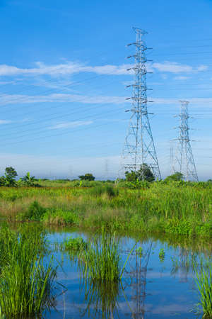 appropriate: High voltage towers. The meadow below. Industry and nature coexist in appropriate Slightly cloudy sky.