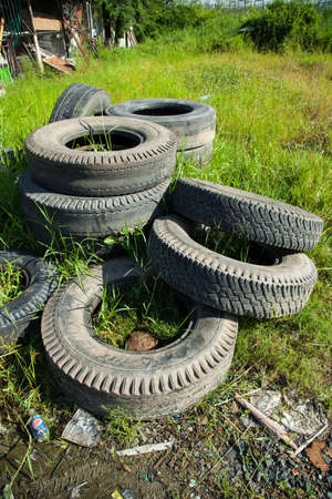 dumped: old tires are being dumped on the lawn. Waste tires are used. Stock Photo