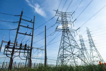 elektriciteit: Hoogspanning torens. De weide hieronder. Industrie en natuur naast elkaar in de juiste Licht bewolkt sky.And zeilde door de lucht.