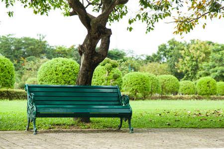 Bankje onder een boom. Een stoel om te rusten. Langs de gang. Binnen het park.
