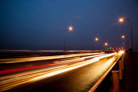 back and forth: Street at night with cars running back and forth on the bridge.