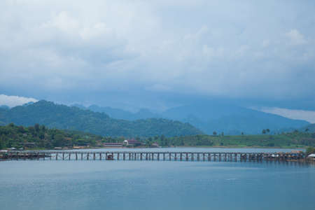 Bridge across the river. The wooden bridge is the second longest in the world. The mountain behind the bridge. photo
